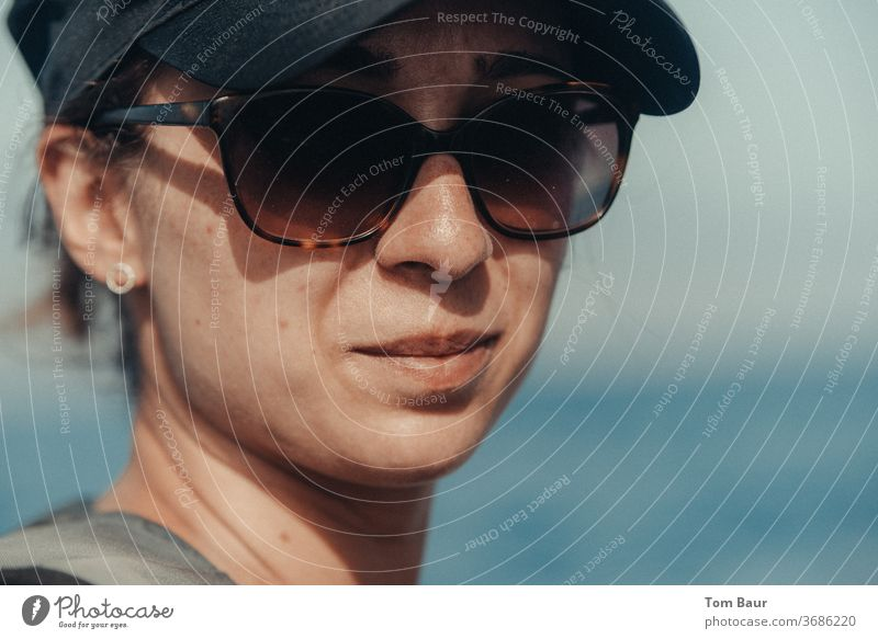 Portrait of a woman with basecap and sunglasses Woman portrait baseball cap Sunglasses Looking into the camera Human being Adults Colour photo Exterior shot