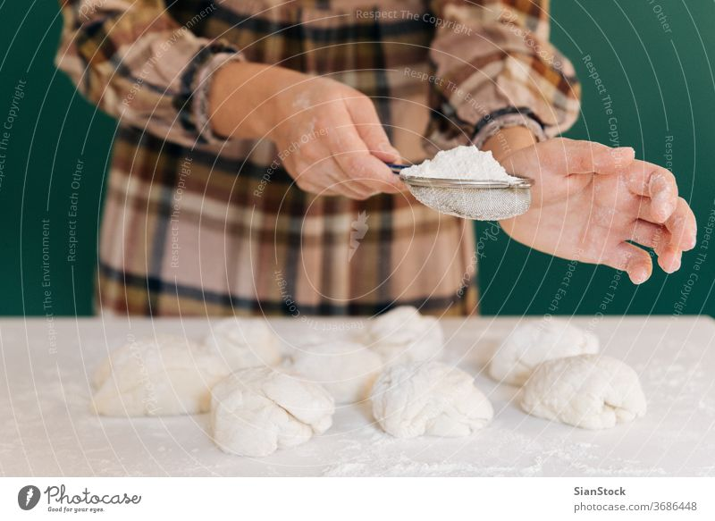 Woman sprinkles flour to handmade pieces of dough for bread, homemade cooking. woman hands white person powder pasta working bake-house food pizza female pastry