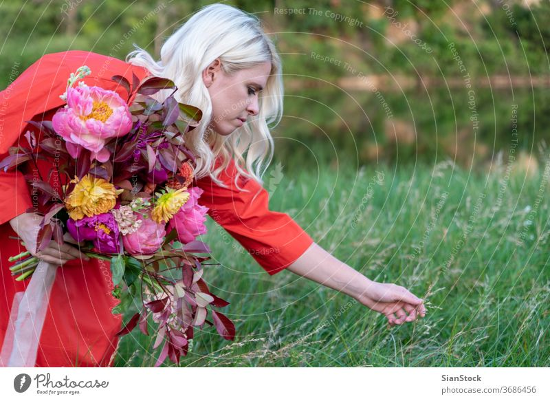 Blonde woman with flowers on the countryside. Portrait photograph Enthusiasm Day Morning Lifestyle Flower Happiness Colour photo Blossom Euphoria Beautiful