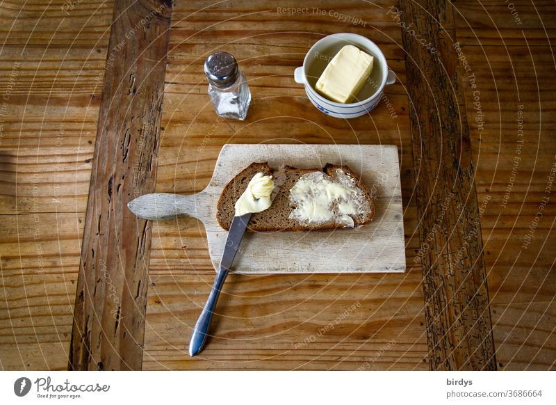 Snack, bread, butter and salt with snack board on a wooden table. Bread and butter Butter Salt vesper board Wooden table Rustic Rural Knives Mixed-grain bread