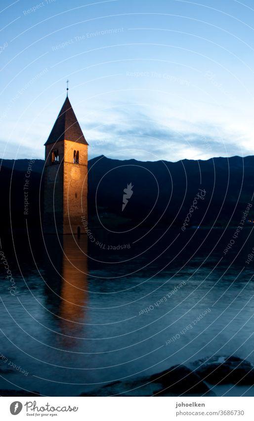 Church in the Reschensee Lake Reschen Church spire drowned underwater Deluge Tower clock Flood evening mood mirror Water Dusk downfall Go under Mountain Alps
