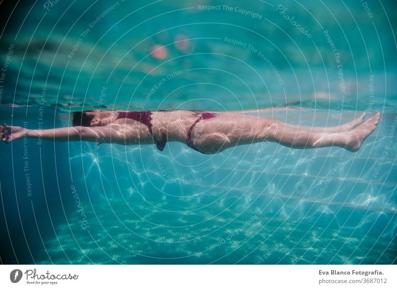 young woman floating in a pool. summer and fun lifestyle underwater swimming bubbles caucasian dive clear health light action wet swimmer blue active person