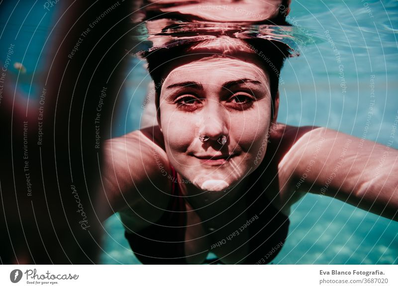 portrait of young woman diving underwater in a pool. summer and fun lifestyle touching hand swimming bubbles caucasian dive clear health light action wet