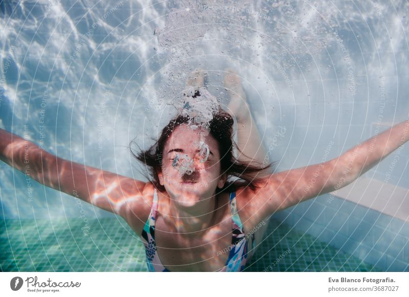 portrait of young woman diving underwater in a pool. summer and fun lifestyle close up swimming bubbles caucasian dive clear health light action wet swimmer