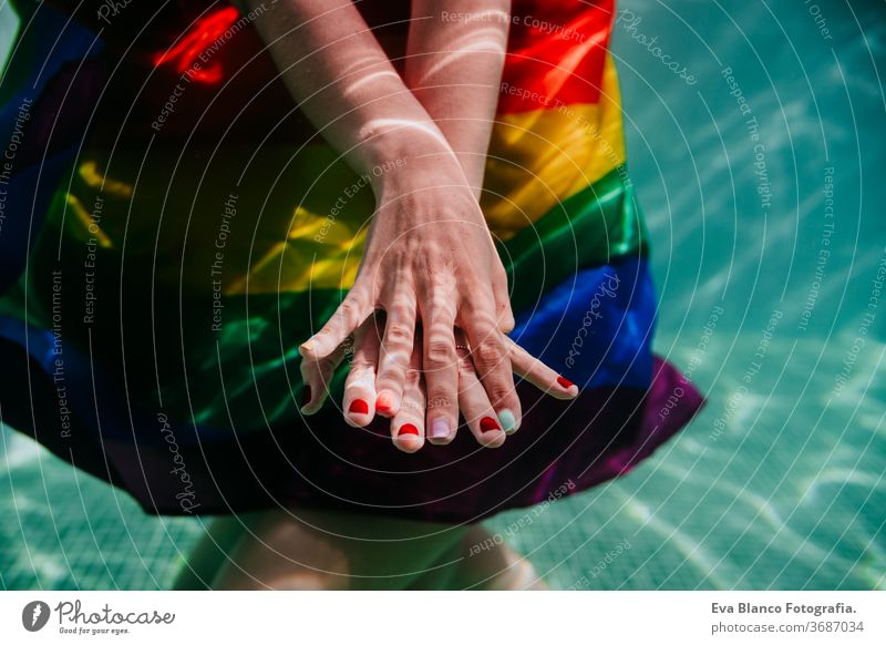 two women at the pool together wrapped with rainbow gay flag. LGBT concept love lesbian underwater swimming pool floating summer lgbt dating romantic bisexual