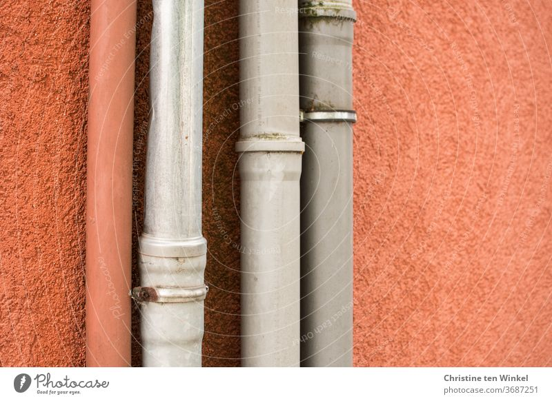 down pipes in front of an orange plastered wall, one orange and three grey Downspout Facade House (Residential Structure) Wall (building) Plastered Orange