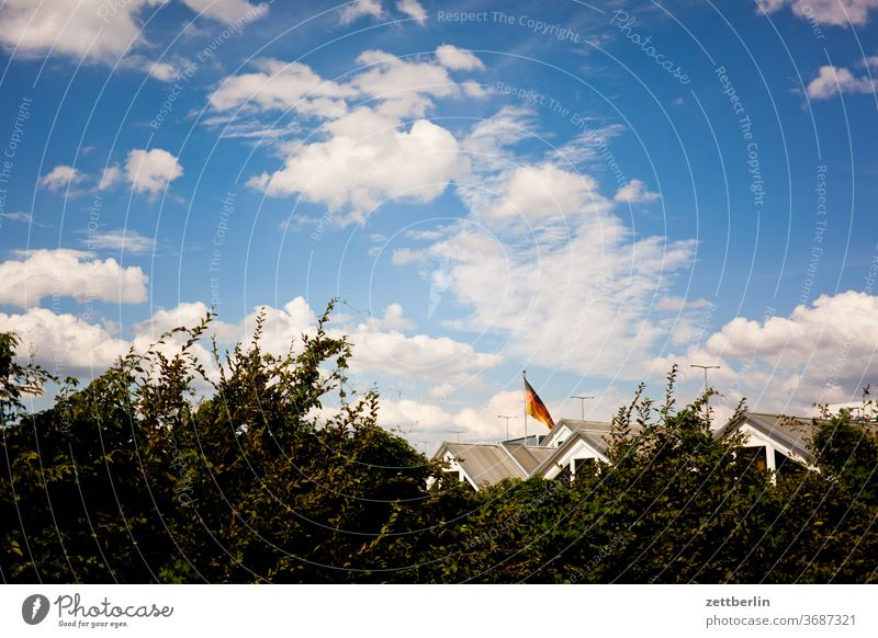 Roofs under German flag House (Residential Structure) Apartment Building Village Town settlement first Residential area Hedge Sky Clouds Summer Flag Germany