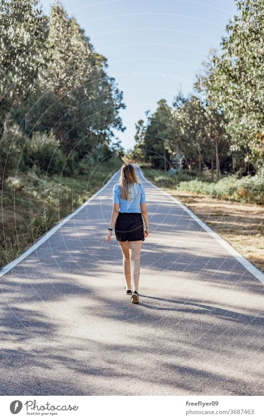 Young caucasian woman walking by an empty road near a forest lifestyle copy space countryside fashion model young blonde sunlight exterior outdoors tranquil