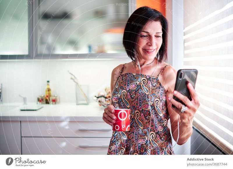 Smiling woman with coffee and smartphone in kitchen morning cup listen music enjoy using female fresh drink gadget browsing surfing home beverage cellphone