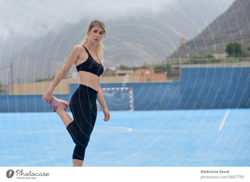 Slim sportswoman stretching legs on sports ground training exercise workout fitness athlete runner slim young female modern wellness wellbeing healthy serious