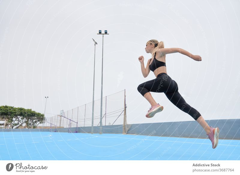 Slim sportswoman jumping on sports ground run training exercise workout fitness athlete slim young female modern wellness wellbeing healthy lifestyle confident