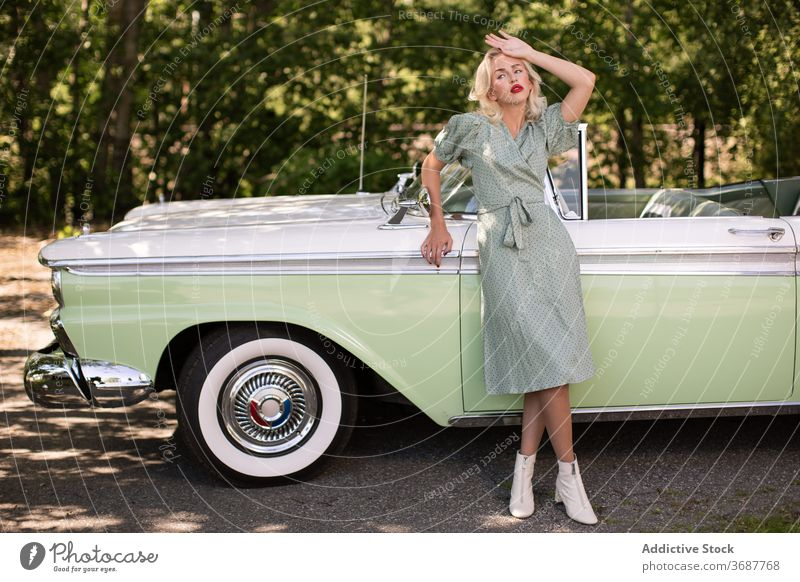 Charming blondie near retro car on street woman vintage style young vehicle classic lifestyle female trendy sunglasses transport fashion confident sensual auto