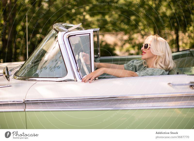 Happy woman driving retro car driver summer smile sunny daytime blond style female positive sunglasses vintage vehicle transport happy joy journey trendy trip