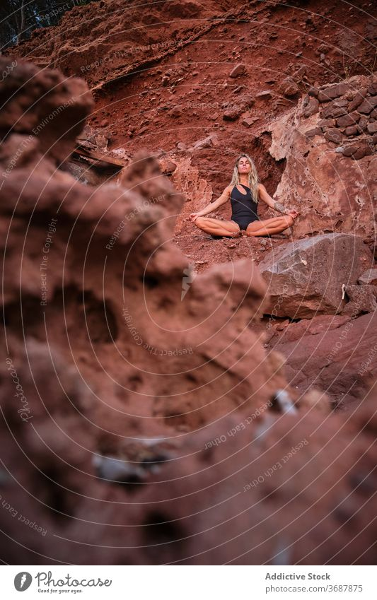 Woman in a swimsuit sitting in meditation in an arid terrain across vertical remain ruins surface isolated abandoned yoga nature fitness meditating relaxation