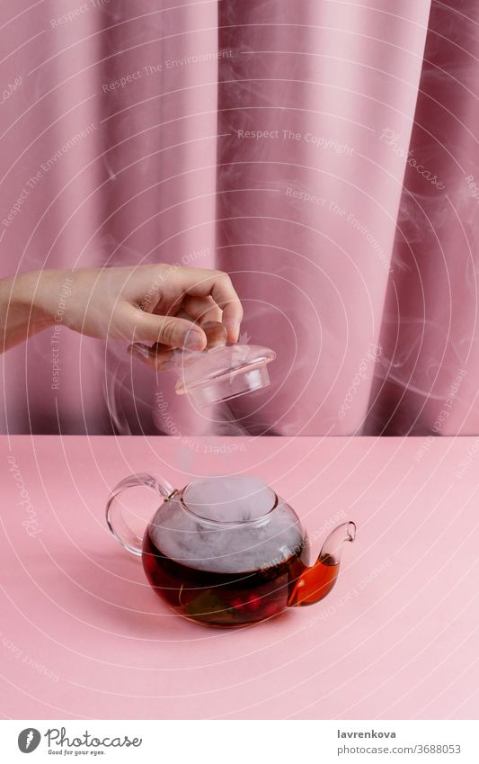 Female hand holding tea pot lid above kettle with the steaming fruit and berry tea beverage hot table hygge drink breakfast serving glass cover tranquillity