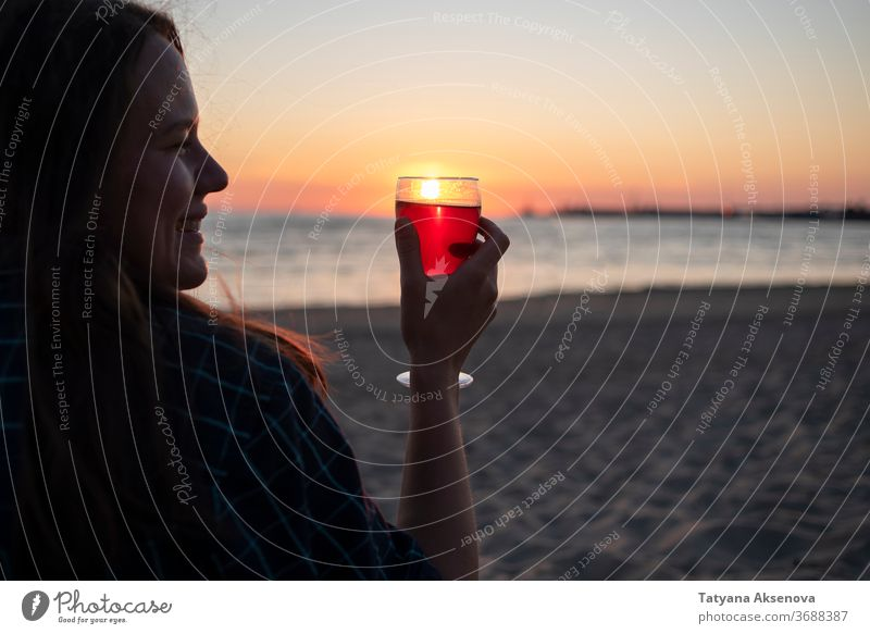 Woman with glass of wine on beach at sunset drink alcohol romantic enjoying slow living relax sea beautiful celebration beverage silhouette romance holiday