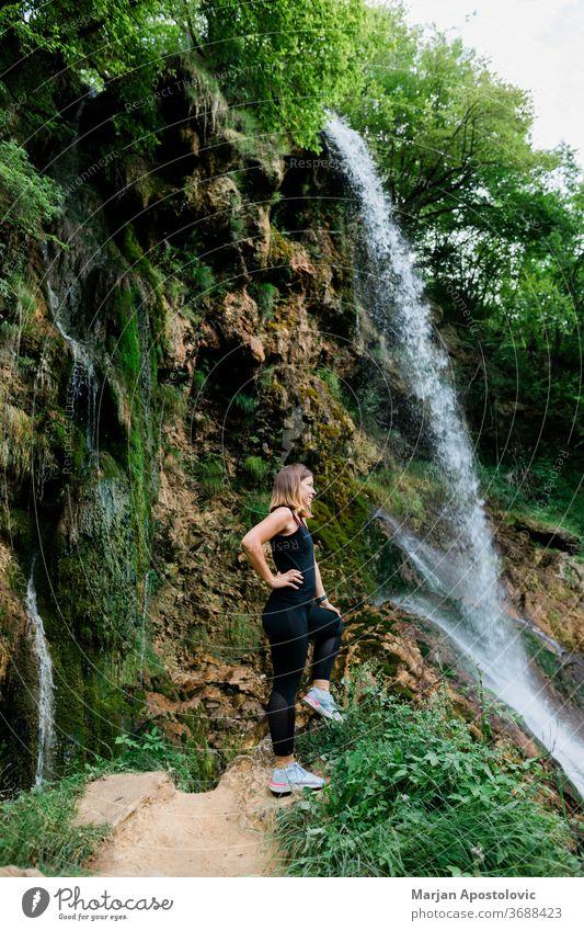 Young female nature explorer standing by the waterfall achievement active adult adventure awe cascade caucasian destination enjoying enjoyment environment