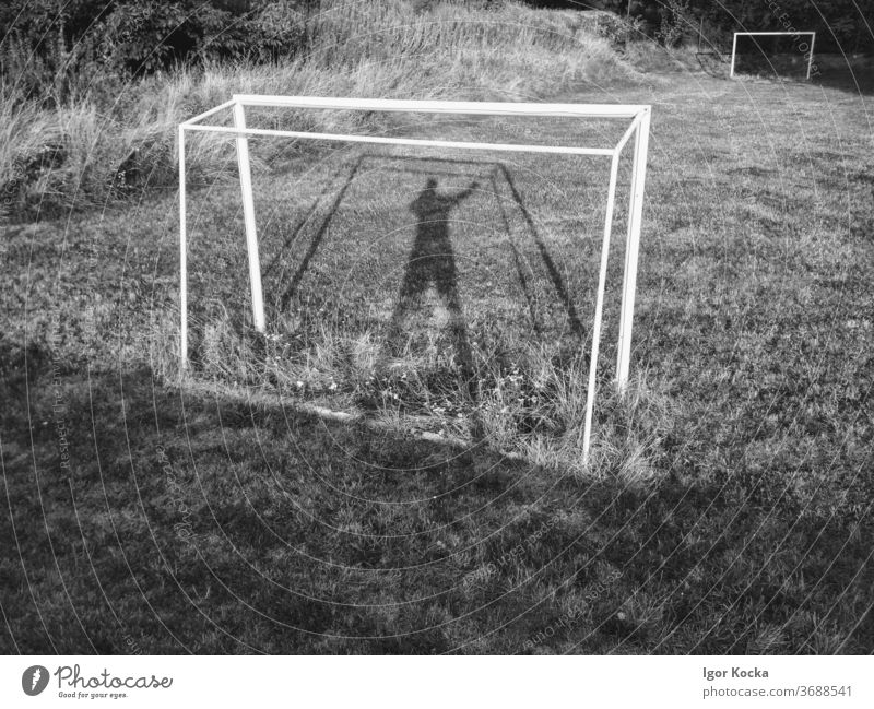 Soccer Goal on Empty Football Field Football pitch football field shadows Goalkeeper Past Deserted obsolete Overgrown Sports Ball sports Black & white photo