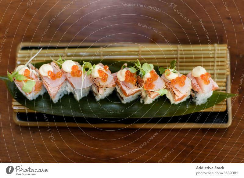Set of colorful sushi rolls on plate set seafood salmon tasty restaurant luxury serve oriental cheese sauce table fish rice cuisine caviar herb fresh savory