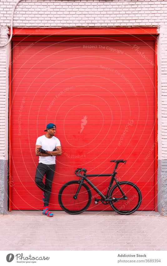 Ethnic hipster man with bicycle standing near wall bike modern style urban trendy confident street red building young african american black ethnic male