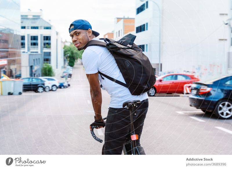 Happy ethnic biker on city street man style urban ride happy modern trendy young african american black male bicycle lifestyle guy positive transport