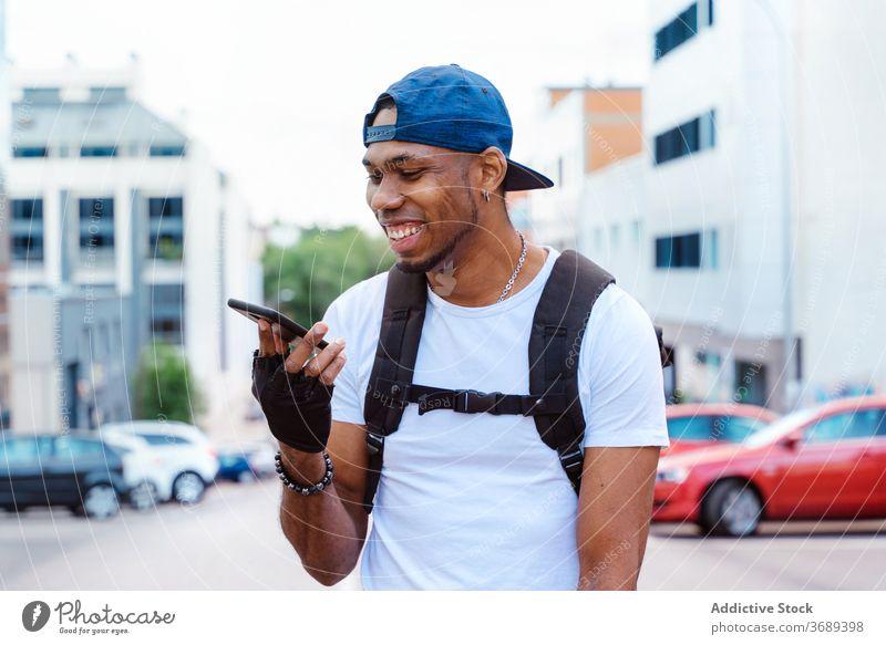 Happy ethnic man using smartphone on street communicate style urban biker message modern trendy happy cheerful optimist lifestyle hipster browsing online