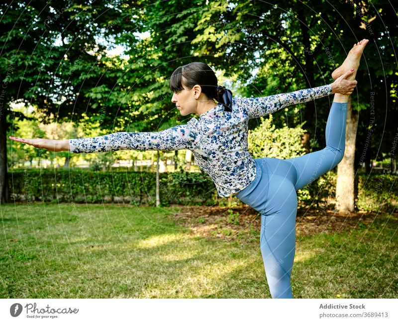Woman doing yoga in Lord of the Dance pose in park lord of the dance woman flexible asana natarajasana concentrate calm female nature healthy practice sunny