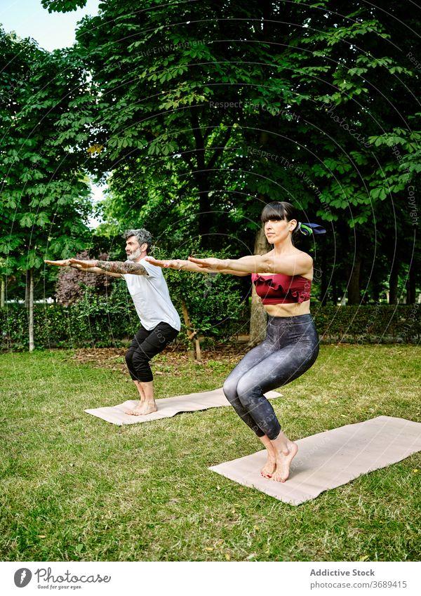 Focused couple doing yoga in Awkward pose in park awkward pose balance asana posture utkatasana together mat green garden healthy practice barefoot harmony