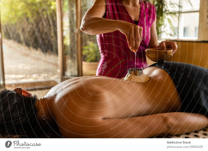 Anonymous woman getting ayurvedic treatment on back ayurveda oil heal pour massage apply therapy female procedure care rehabilitation therapist professional
