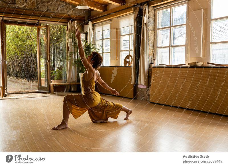 Serene woman practicing yoga in Crescent Lunge position anjaneyasana crescent lunge pose practice flexible serene harmony mindfulness female studio barefoot