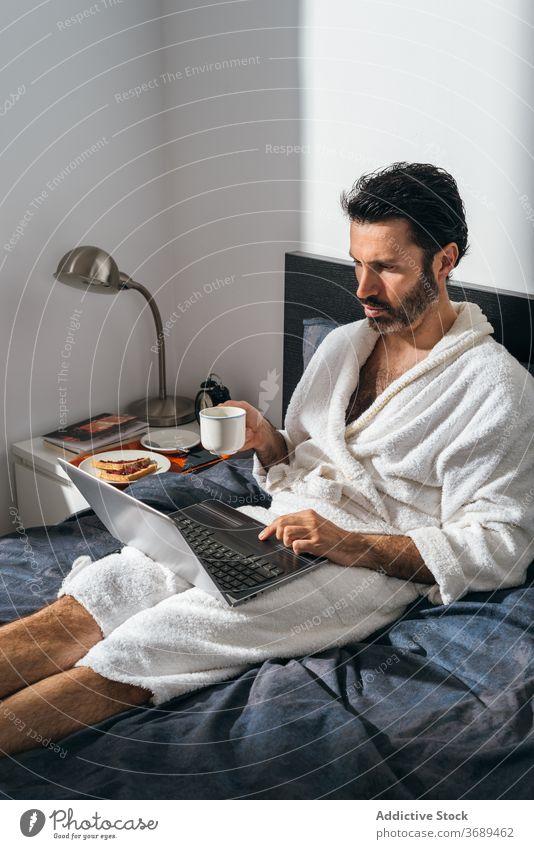Calm man having breakfast on bed freelance coffee laptop work remote bathrobe using male businessman cup fresh morning drink device internet comfort online