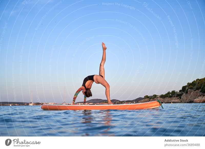 Flexible woman doing yoga on paddleboard sunset pose surfer balance sea female water healthy nature harmony relax tranquil serene sky calm ocean peaceful lady