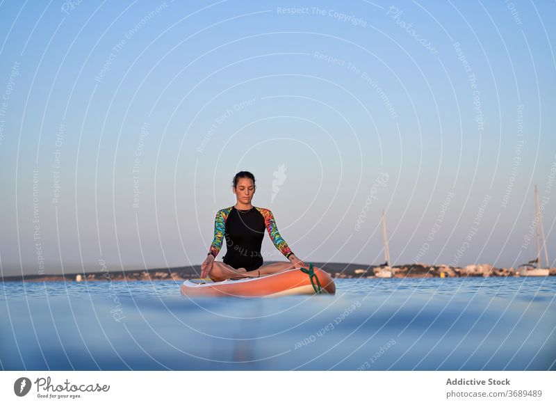 Flexible woman doing yoga in lotus pose on paddleboard sunset surfer balance sea female water healthy nature harmony relax tranquil serene closed eyes sky calm