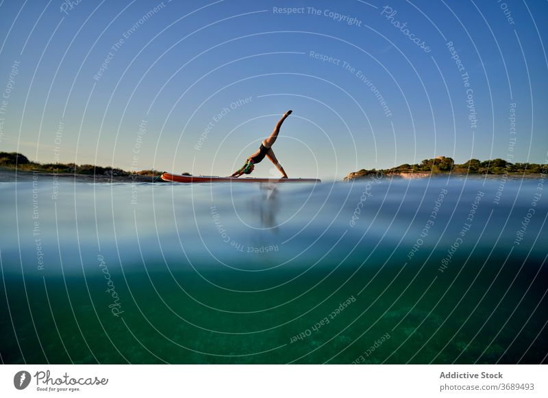 Flexible woman doing yoga in Downward Facing Dog pose on paddleboard sunset silhouette downward facing dog surfer balance sea female water healthy nature