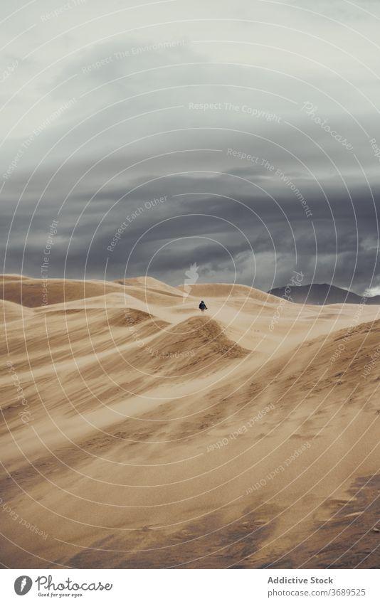 Anonymous traveler on sandy dunes on cloudy day tourist national park desert landmark tourism colorado usa united states america vacation walk person landscape