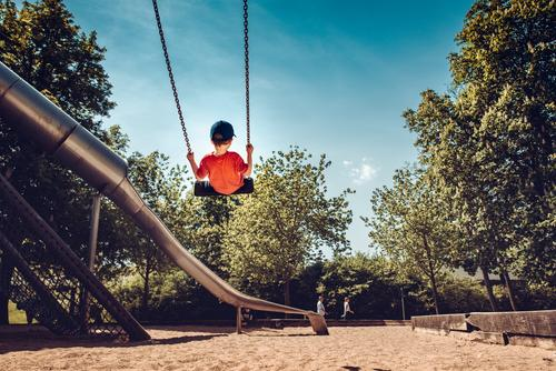 Boy on a swing on the playground Boy (child) Child rock Swing Playground Playing Tall Chain Adventure foolhardy cap from behind Slide Comical muck about huts