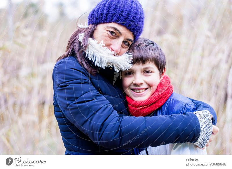 Mother with wool hat hugging son with love outdoors 2 caucasian young mother smiling people woman family cheerful beautiful senior lifestyle mature portrait