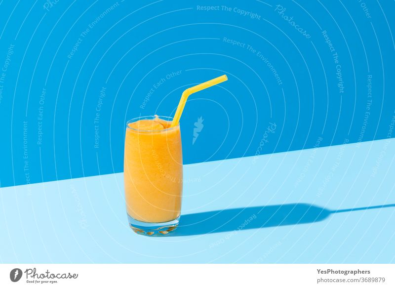 Mango smoothie on blue color. Summer drink. Mango shake with a straw background beverage bright cocktail cold colors copy space cut out delicious dessert detox