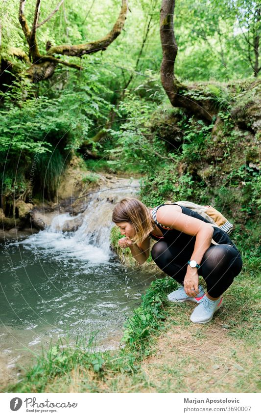 Young female nature explorer drinking water from the spring active activity adult adventure backpack backpacker creek ecology exploring forest freedom freshness