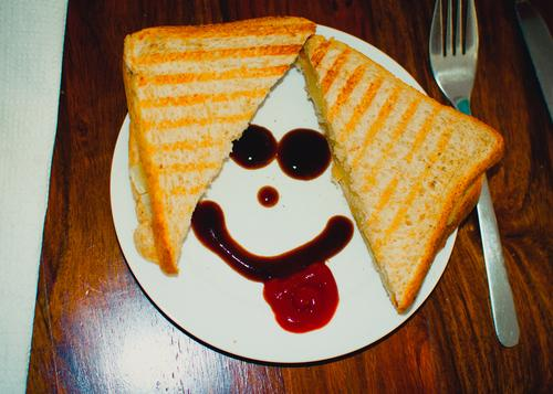 Breakfast Smiley, A shared bread on the plate. With ketchup a smiley face. On the right a fork on a wooden table. breakfast snack Food Colour photo Delicious