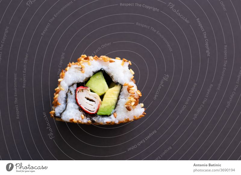 Closeup of a single piece of homemade not perfect sushi roll. Isolated on dark black background. Roll containing avocado, surimi, cucumber and fried sesame seeds