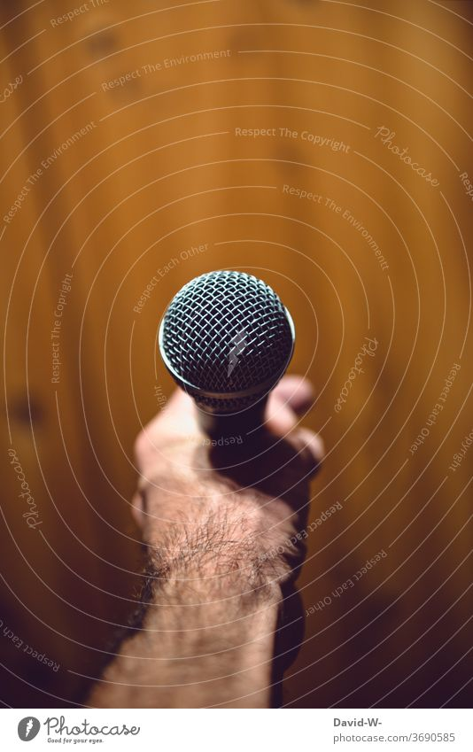 Man holds a microphone in his hand ready to speak Microphone Speech present Moderator Business Colour photo Interior shot To talk Communicate Event Speaker