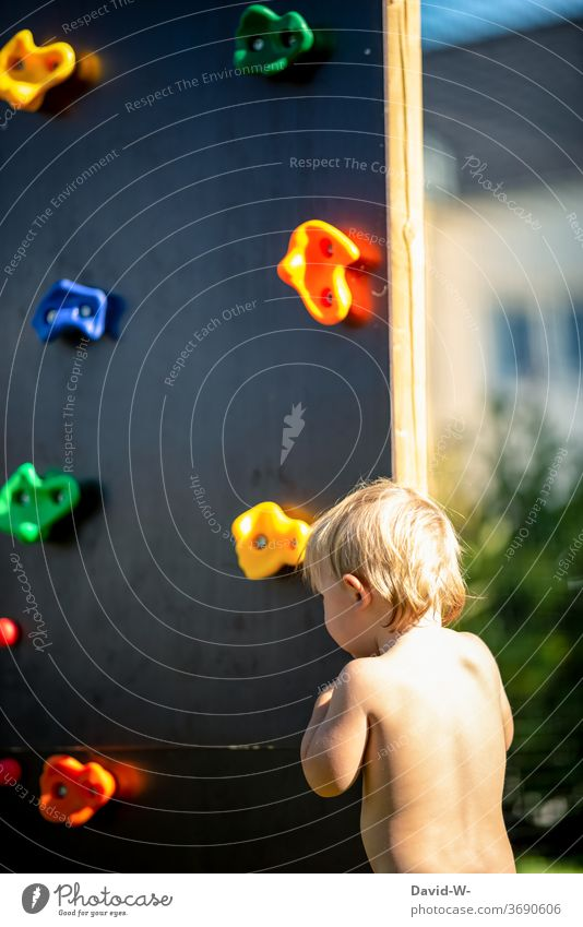 Child standing in front of a climbing wall Playing Climbing Infancy Climbing wall Playground Summery ardor Boy (child) anxiously timid cautious