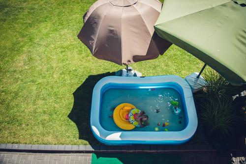 Child bathes in the garden in a paddling pool surrounded by parasols that provide shade Paddling pool Sunshade shade dispenser sunny Quarantine Home Infancy