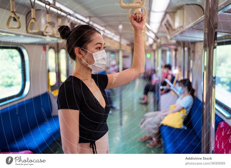 Asian woman in mask in train travel coronavirus public transport outbreak protect commute female ethnic asian modern passenger stand trip journey safety covid