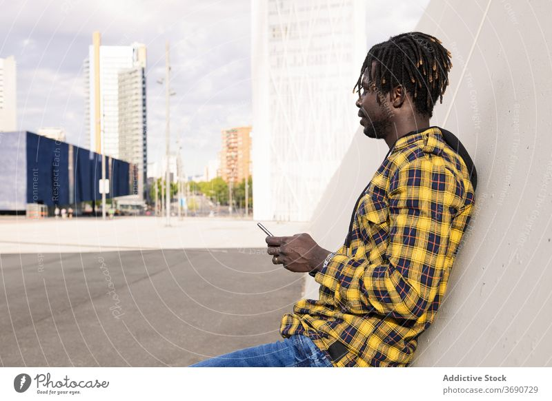 young african man with his phone on the city person holding black mobile technology male lifestyles modern cellphone smart smartphone urban american guy