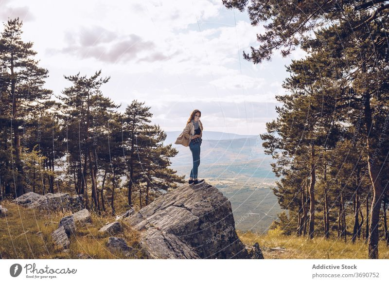Traveling woman on stone in forest rock tourist mountain vacation traveler adventure trip female destination holiday freedom stand relax enjoy admire recreation