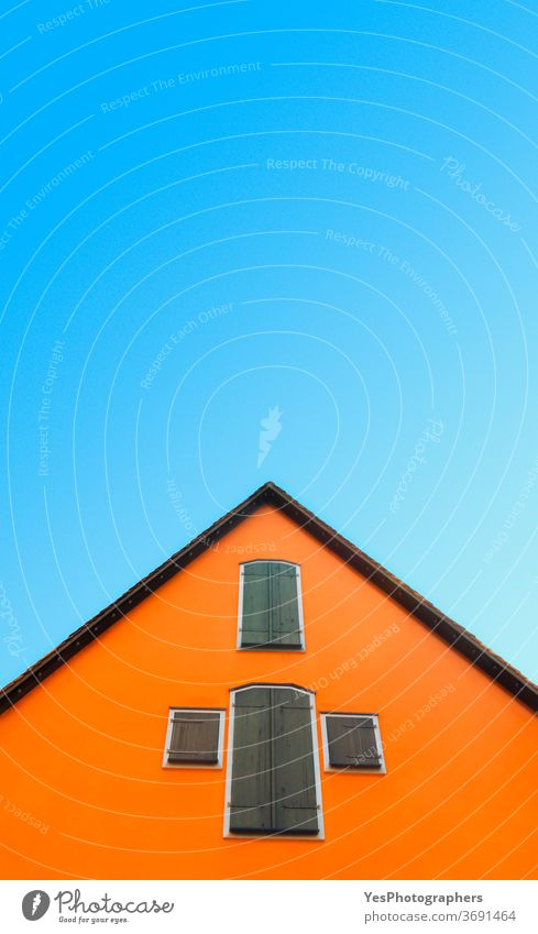 Orange house against blue sky. House with orange walls minimalist. German architecture Germany abstract antique attic bottom-up bright building clear colors