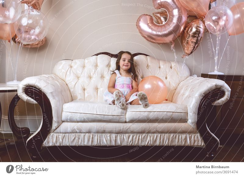 3-year-old birthday girl playing with her balloons on the couch Child Toddler Girl 3 - 8 years Birthday celebration Balloon Smiling one person Couch indoors