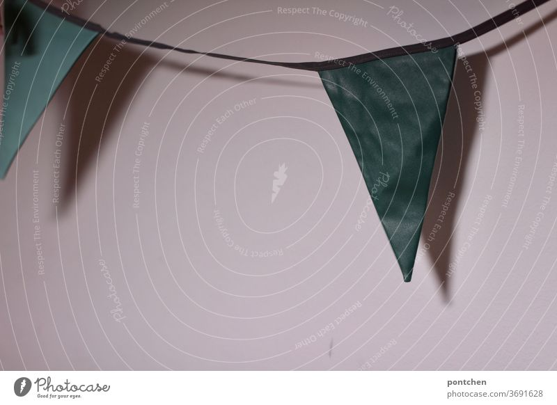 A pennant chain casts a shadow on a white wall. Decoration, celebration Green tones Shadow celebrations Wall (building) White Feasts & Celebrations dwell
